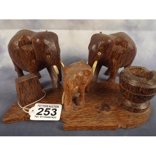 253 - Two small carved wooden elephants with tusks together with elephant desk set...