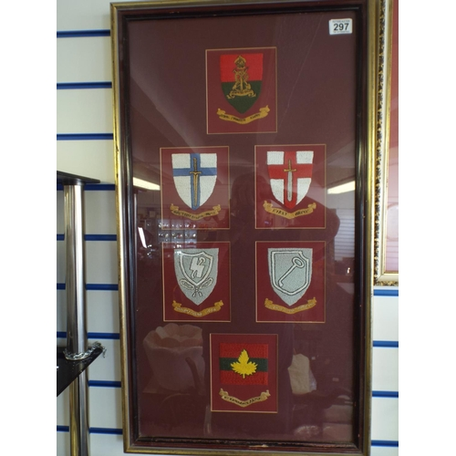 297 - Embroidered army regimental badges behind glass in frame...
