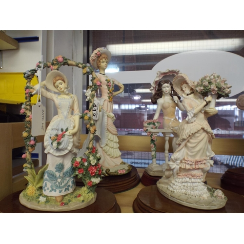 413 - Four resin pretty ladies on wooden bases...