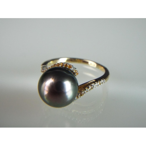 9 - 14ct Yellow gold ring set with a large Tahitian pearl,  White Sapphires to shoulders. 'N'...