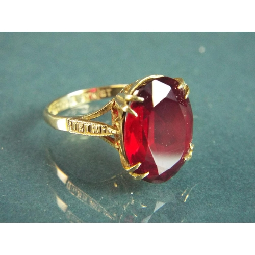 56 - 9ct Yellow gold ring set with a large synthetic Ruby which measures 15 x 12 mm.  Finger size 'M-5'  ...