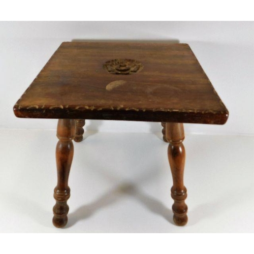 27 - A small low level table with carved rose decor signed to underside TH dated 1961...