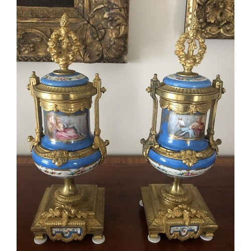 1064 - A pair of 19thC hand painted gilt mounted porcelain urns. 35cms h. Marked to the rear Brunfaut.