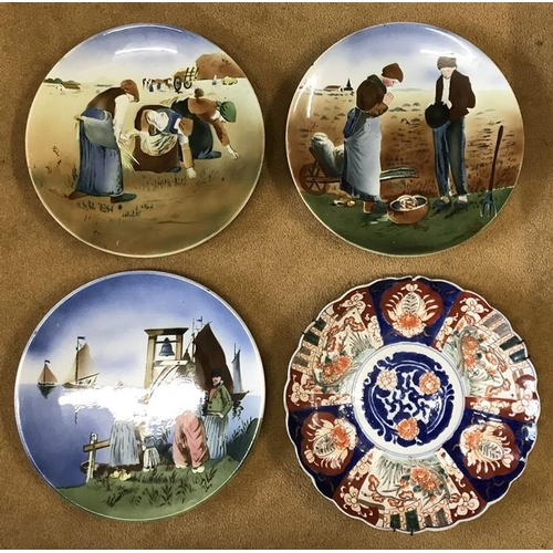 35 - Four hand painted glazed wall mounted plates to include 3 Dutch scenes of muted brown and blue and a...