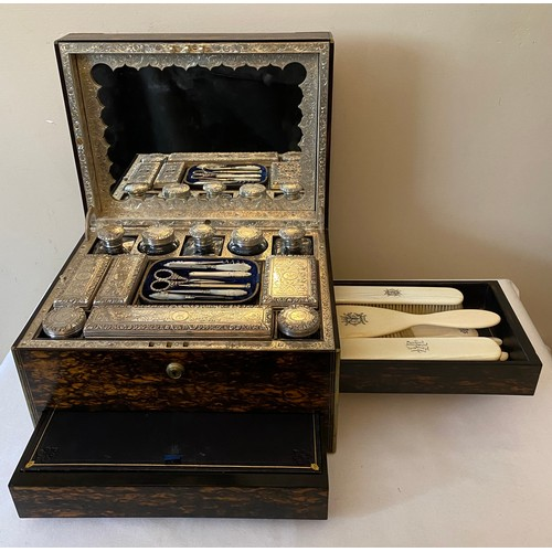 A fine quality Victorian coromandel wood dressing case with eleven extensively engraved silver topped glass jars and containers all London 1864 maker probably William Neal. Crested with engraved initials. Two secret drawers, a side one with ivory brushes by Asprey 166 Bond Street, the other lower front silk lined for jewellery. Fold down removable mirror with a spring release to reveal secret document pouch and makers stamp W H Tooke of Liverpool.  33.5cms l x 21cms h x 25.5cms d.
