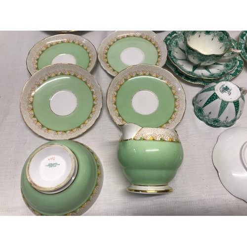 6 - Two part tea sets. Copeland Grosvenor China green and gilt comprising 2 cake plates 24cms, 12 side p...