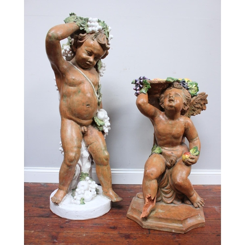 62 - Two matched early 20th century painted terracotta garden ornaments one modelled as a cherub, the oth...