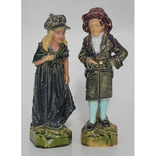 45 - A pair of 19th century continental glazed pottery figures of a girl and boy, decorated in polychrome...