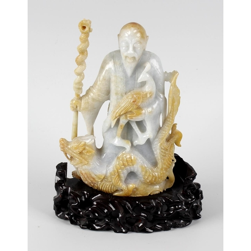 105 - A Chinese carved jade figurine, modelled as an elderly bearded male stood behind a dragon, holding p...