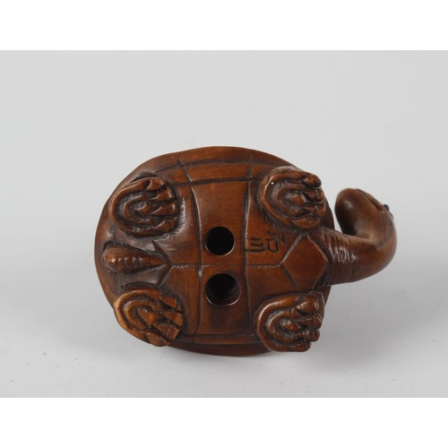 108 - A Japanese carved boxwood netsuke, modelled as a small oni or monkey, wearing a tortoise carapace di...