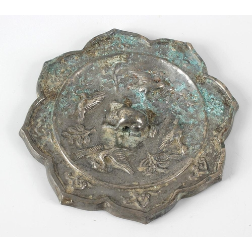 111 - A Chinese cast mirror. Of eight-lobed petal form, the slightly dished field decorated in relief with...
