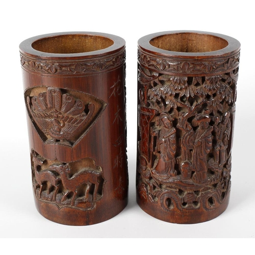 115 - A pair of Chinese bamboo brush pots each with carved fronts depicting figures gathered beneath prunu...