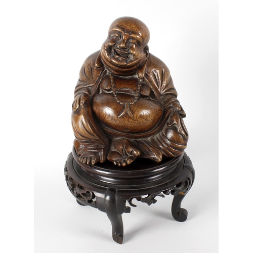 117 - A Chinese carved bamboo figure of Hotei/Budai, in traditional seated pose, upon an associated carved...