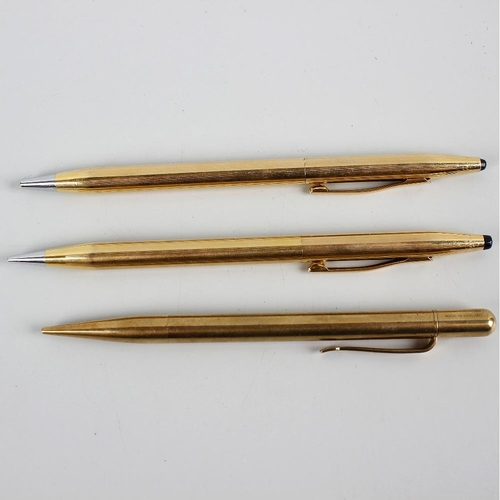 125 - Three yellow metal mechanical pencils. Comprising a pair of Cross gold plated examples, each of simi...