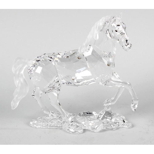 14 - A Swarovski crystal horse figurine, modelled with one foreleg raised on an integral naturalistic bas...