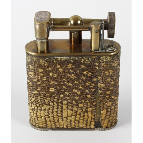 169 - A novelty brass desk lighter, of oblong form, the body with snakeskin overlay, 4.5 (11.5cm) high.  <...