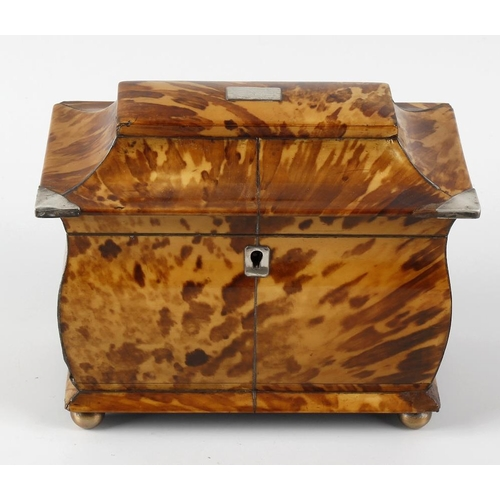 215 - An early 19th century blond tortoiseshell tea caddy. The hinged spreading cover with vacant central ...