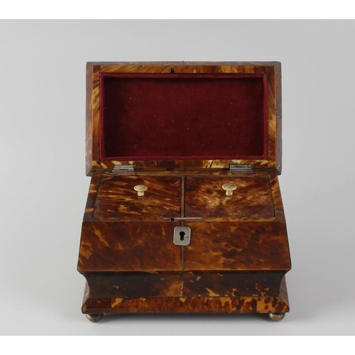216 - An early 19th century blond tortoiseshell tea caddy. The pewter-strung hinged spreading rectangular ...