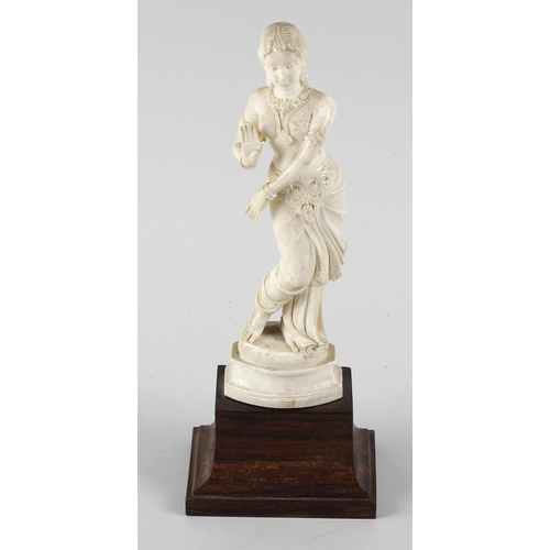 237 - An ivory figure, modelled as a female Indian dancer with open palm outstretched, on wooden plinth, 7...