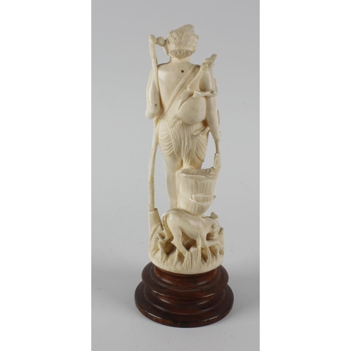 243 - An ivory figure, modelled as a huntsman with bow and arrow, on circular wooden plinth, 6.75 (17cm) h...