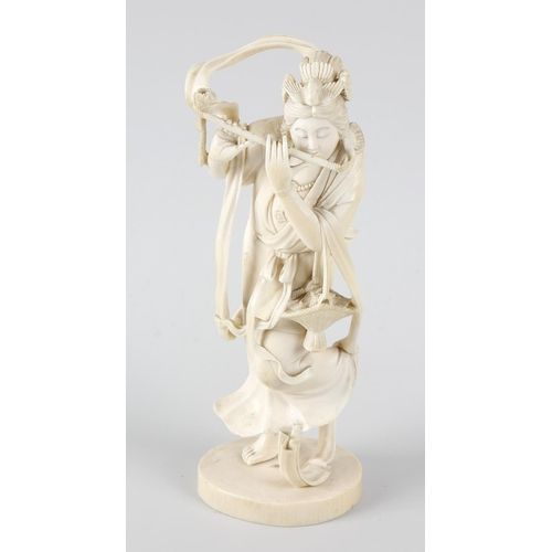 245 - A good Japanese Meiji period ivory okimono, modelled as a female musician playing the flute, on circ...