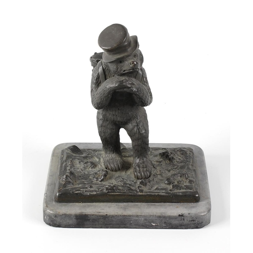 271 - A 19th century cast bronze table vesta modelled as a bear standing upon his hind legs, wearing a hat...