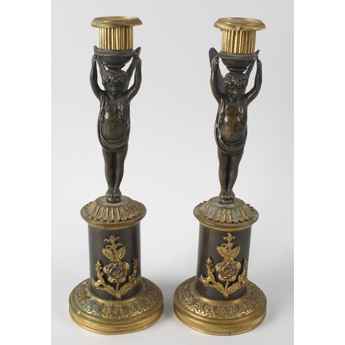 272 - A pair of early 19th century French bronze candlesticks, the stems modelled as two putti with arms r...