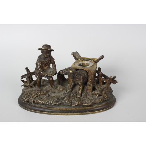279 - An unusual 19th century bronze inkstand, modelled as a young child feeding a dog standing within its...
