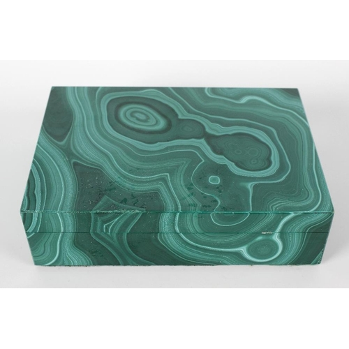 299 - A malachite box and cover of rectangular form, the hinged opening cover lifting to reveal a black sl...