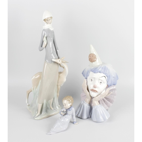 31 - A group of four Lladro figurines, the first example modelled as the bust of a sad clown resting his ...