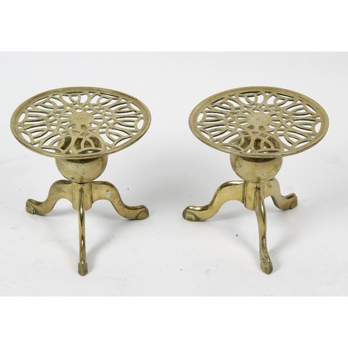 319 - A pair of brass trivets, each having a pierced circular top over a spherical stem and tripod base, e...