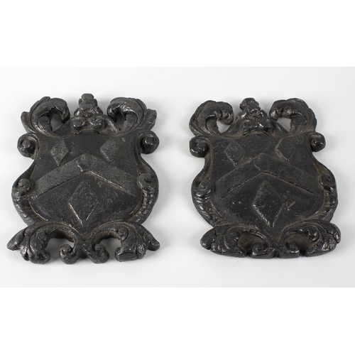 320 - A pair of cast lead plaques, each modelled as a coat of arms with foliate and scrollwork surrounds a...