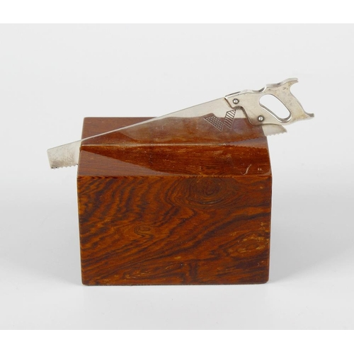 334 - An Asprey of London novelty paper weight, modelled as a saw imbedded in a block of wood, the silver ...