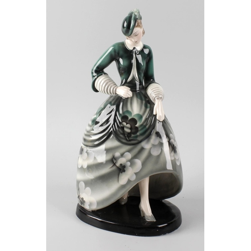 34 - A Goldscheider figurine, modelled as a young woman in green floral dress, dress marked 'Claire Weis'...