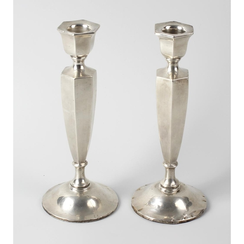 340 - A pair of George V silver candlesticks, each of octagonal tapering form leading to the knopped and s...