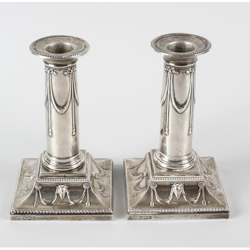 341 - A pair of Edwardian silver candlesticks, decorated with ribbon swags to the plain stems and raised u...