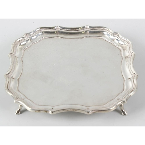 364 - A silver salver, of square form with a Chippendale style rim to plain centre, raised on four stylise...