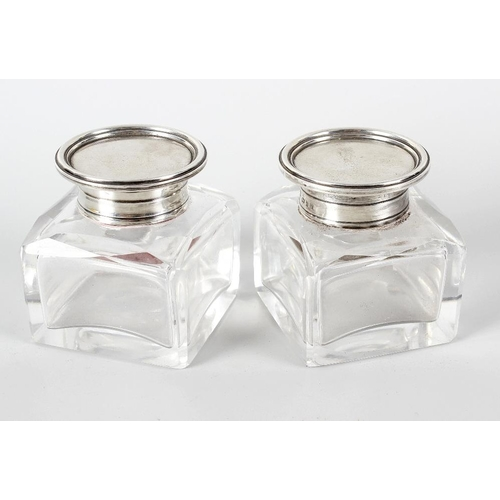 377 - A pair of George V London 1919, hallmarked silver topped glass inkwells, the hinged covers with plai...