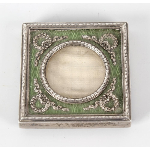 381 - A small easel style white metal and green enamel panelled photograph frame, the glazed circular pane...
