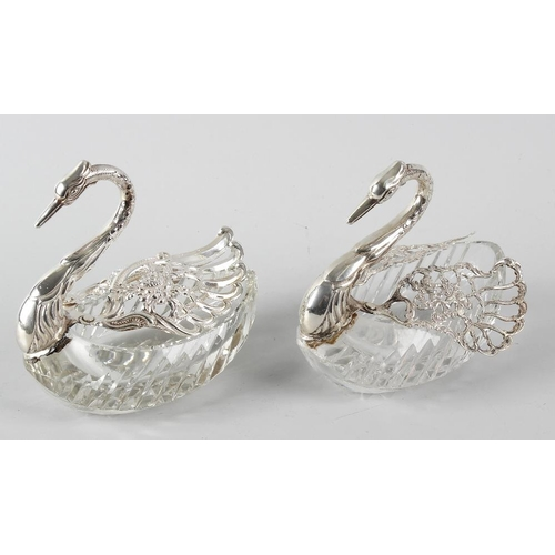 382 - A pair of sweetmeat baskets modelled as swans, having moulded glass bodies and pierced sterling silv...