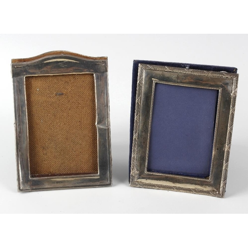 384 - Two hallmarked silver photograph frames, the first of rectangular form, with bevelled edges and lobe...
