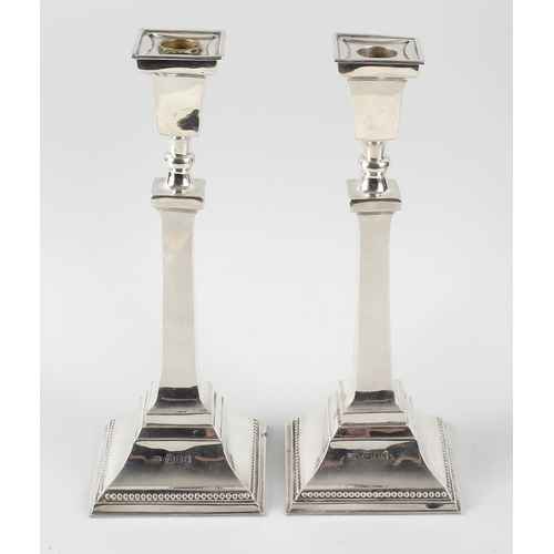 395 - A pair of George VI silver candlesticks, the square stepped bases with beaded rim, rising to the con...