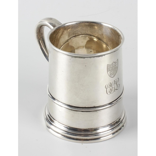 397 - A silver mug, the body of tapering form with moulded girdle, having stepped base and scroll handle, ...