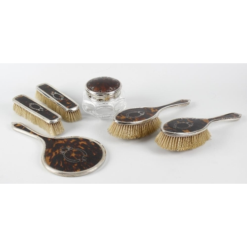 413 - A silver and tortoiseshell six-piece dressing table set, comprising a hand held mirror of circular f...