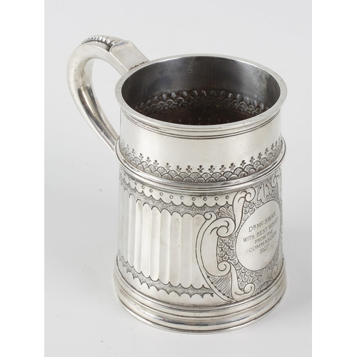 415 - A silver mug of slightly tapering form, with scrolling handle upon a moulded rim, the reed panelled ...