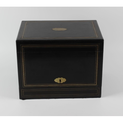 425 - A late 19th century ebonised decanter box, having banded brass inlay and a vacant cartouche and escu...