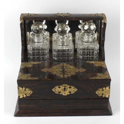 426 - A late Victorian coromandel three-bottle tantalus, having a hinged front opening to a compartmented ...