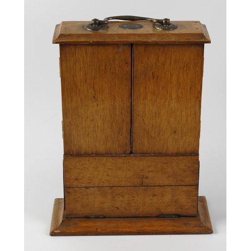 432 - A 19th century oak key box, of rectangular form on spreading base, with plain drop carry handle to t...