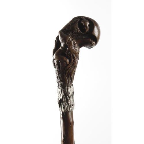 463 - A 19th century black forest carved walking cane, the carved wooden handle depicting a gnome and a mo...