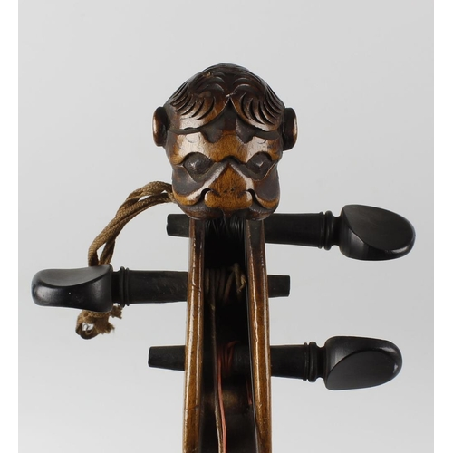 514 - A late 19th/early 20th century violin, having a carved lion head scroll terminal, 23 (58.5cm) long, ...
